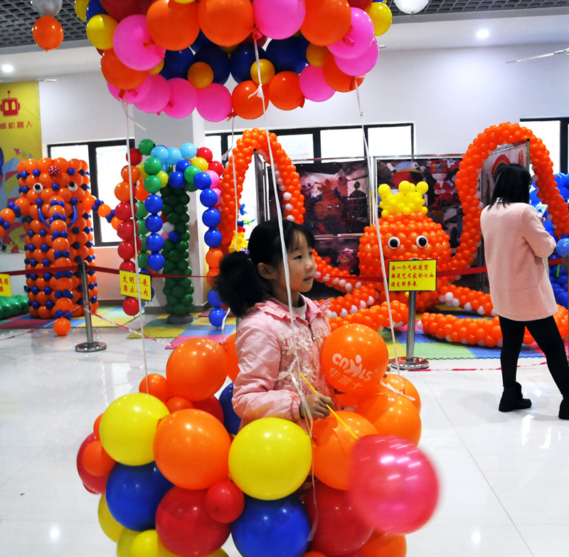 十冬腊月,细雨霏霏。11月22日上午,首届气球艺术节在市文化馆二楼拉开了序幕。此次气球展是由市文化馆和市深港文化艺术中心联合举办。 活动现场,人声鼎沸,室内场馆站满了络绎不绝的人群。充满童趣的动物气球主题馆和现场气球DIY相结合,场景新颖别致,成千上万只气球编织出了大树、大象、大章鱼、长颈鹿等形状各异的造型,充分融入了艺术想象,令人啧啧称奇。一个个形状统一的彩色气球,经过气球创意大师的巧手后,瞬间变成各种各样活泼动人的卡通造型,不少市民开心地说真没想到气球还可以这样玩,感觉挺新奇的,对于开发孩子的思维